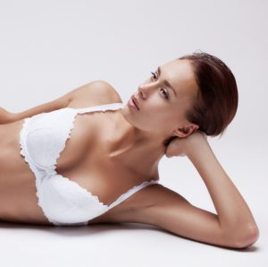 Upper Torso of Model in White Bra Reclining on Floor - Breast Implants Shifted