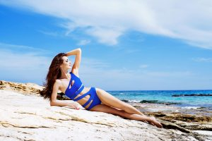 Model in Blue Bathing Suit Lounging on Sandy Beach Copy