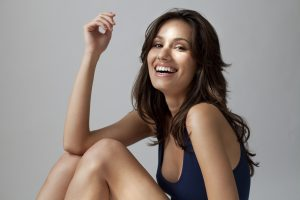 Smiling Model Sitting with Knees Bent and Arm on Knee