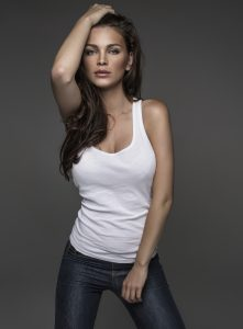 Sexy Model in White Tank in Jeans Combing Hair Back