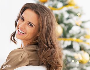 Brunette Smiling Over Shoulder In Front of Christmas Tree