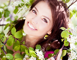 Cute Brunette's Face Surrounded by Flowers and Green Leaves